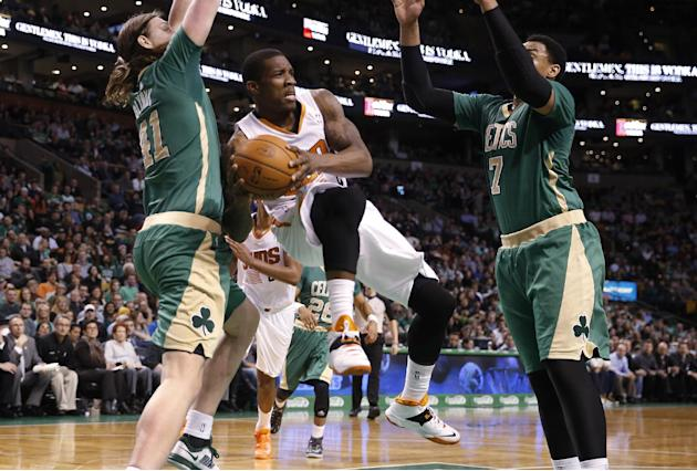 Phoenix Suns guard Eric Bledsoe looks to pass the ball off between Boston Celtics' Kelly Olynyk (41) and Jared Sullinger during the second half of the Suns' 87-80 win in an NBA basketball game