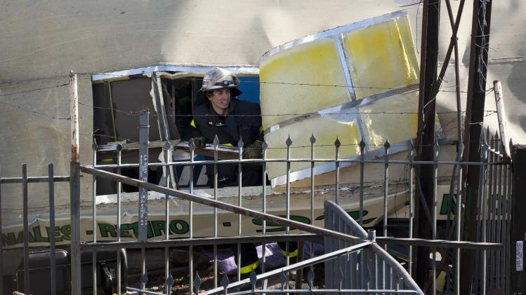 A rescue worker looks out from a cut made on the roof of a bus that collided with a train in Buenos Aires, Argentina, Tuesday, Sept. 13, 2011. At least seven people were killed and over 162 injured in a rush-hour crash involving two trains and a bus whose driver drove around barriers in an attempt to beat them across the tracks, Argentine authorities said. (AP Photo/Victor R. Caivano)