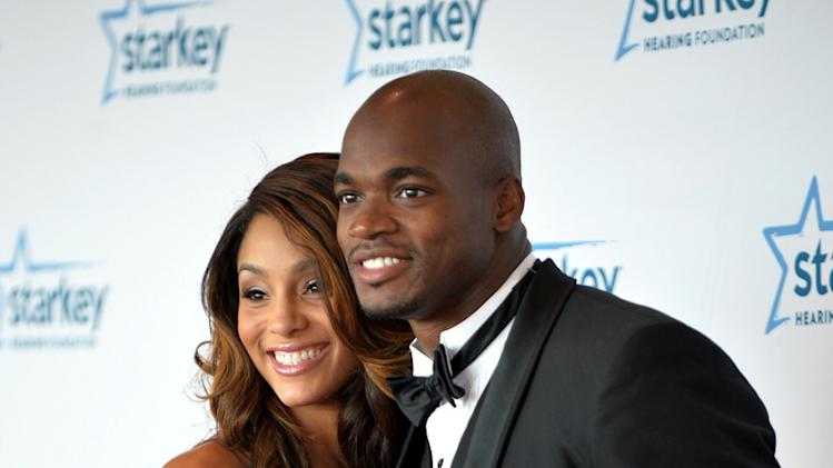 In this July 20, 2014 photo, Minnesota Vikings running back Adrian Peterson poses with his wife Ashley Peterson during the Starkey Red Carpet Gala in St. Paul, Minn. Adrian Peterson has arrived at training camp with a different look: a ring on his finger. The star running back reported Thursday, July 24, 2014 with the rest of the Vikings to the Minnesota State University campus and confirmed he married his longtime girlfriend, Ashley Brown, just five days earlier
