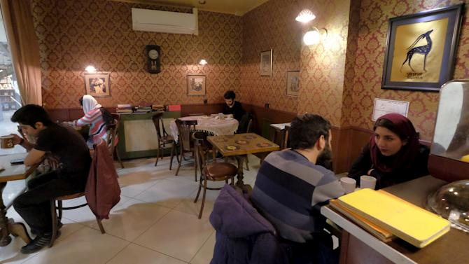 Iranian youths sit at a coffee shop in central Tehran, Iran