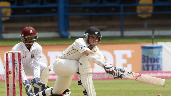 New Zealand's opening batsman Tom Latham, right, sweeps a delivery off West Indies Sulieman Benn as captain and wicket keeper Denesh Ramdin, left, looks on during the opening day of the second cricket Test match in Port of Spain, Trinidad, Monday, June 16, 2014. (AP Photo/Arnulfo Franco)