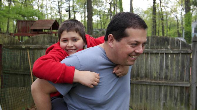 Stuart Chaifetz plays with his son Akian Chaifetz, 10, in the backyard of their home in Cherry Hill, N.J., Wednesday, April 25, 2012. After Chaifetz was told that his son Akian was acting violently at his New Jersey school he decided to investigate. Akian has autism, as do the rest of the students in the class. This prevented him from being able to explain to his father if anything had been happening to him at school. Chaifetz decided the only way to find out what was behind the outbursts was to send his boy to school wearing a hidden audio recorder. (AP Photo/Mel Evans)