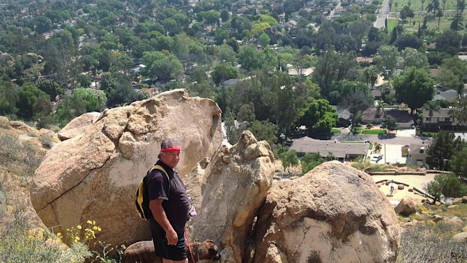 Ramon Llamas and his dog Mole stand at the boulder on Mt. Rubidoux near Riverside, Calif., on Monday, March 25, 2013 where he and his dog Mole found a hiker who's foot had been trapped in boulders. Riverside fire Capt. Bruce Vanderhorst says the man is being treated Tuesday for severe dehydration.  (AP Photo/Riverside Press Enterprise, John Asbury) MAGS OUT