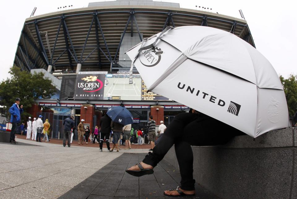 Patrons gather outside of Arthur Ashe stadium during a rain delay at the U.S. Open tennis tournament in New York, Wednesday, Sept. 7, 2011. (AP Photo/Charles Krupa)