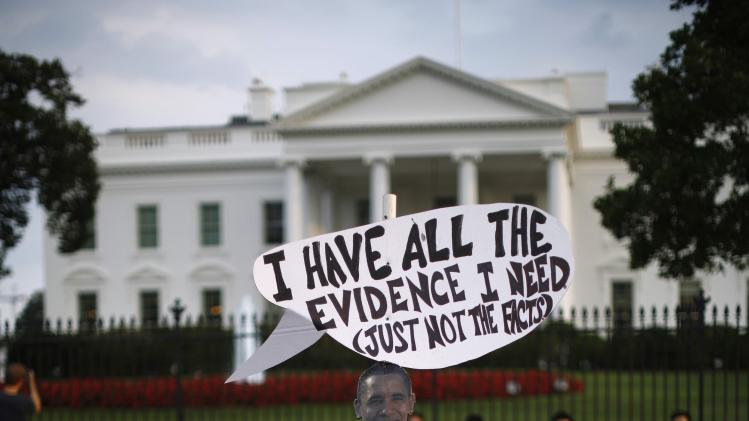 Protesters against U.S. military intervention in Syria are pictured as they set up a cardboard cutout of U.S. President Obama, during a rally outside the White House in Washington