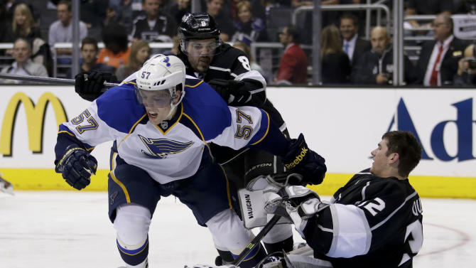 St. Louis Blues' David Perron (57) is pushed by Los Angeles Kings' Drew Doughty as Los Angeles Kings goalie Jonathan Quick sits on the ice during the third period in Game 3 of a first-round NHL hockey Stanley Cup playoff series in Los Angeles, Saturday, May 4, 2013. The Kings won 1-0. (AP Photo/Jae C. Hong)