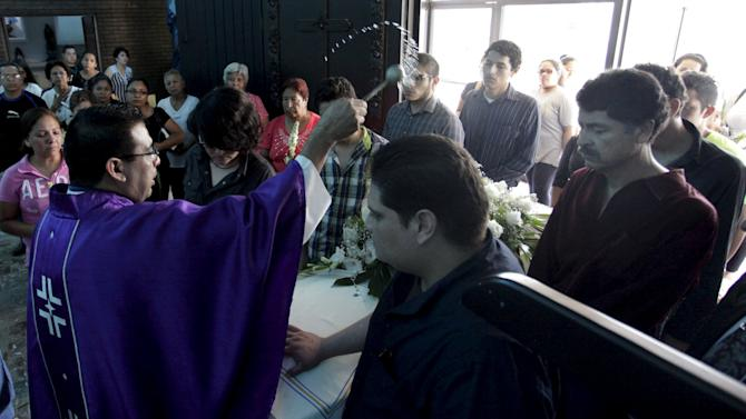 A priest sprinkles holy water on coffin of Martha Armadillo, one of the pilgrims who died in an accident, during her funeral mass at a church in Monterrey, Mexico
