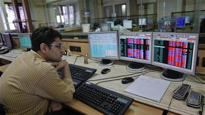 A broker monitors share prices at a brokerage firm in Mumbai