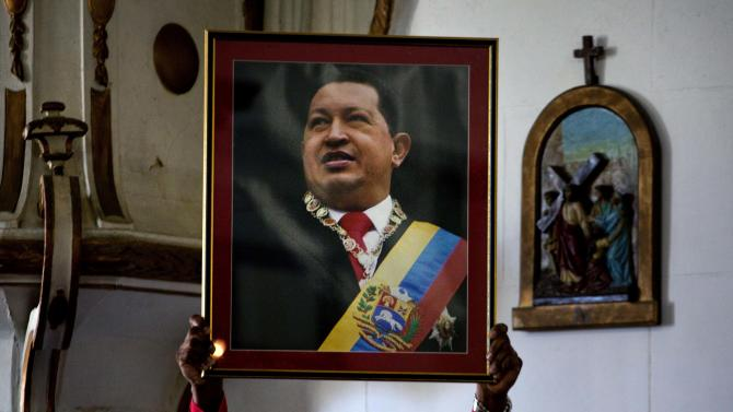 """A Venezuelan embassy worker holds up a framed image of Venezuela's ailing President Hugo Chavez during the monthly Catholic service devoted to the sick at the Church of Our Lady of Regla, in Regla, across the bay from Havana, Cuba, Tuesday, Jan. 8, 2013. Venezuela's government said Monday, Chavez is in a """"stable situation"""" in a Cuban hospital receiving treatment due to a severe respiratory infection. The update came as other government officials reiterated their stance that the president need not be sworn in for a new term as scheduled this Thursday and could instead have his inauguration at a later date. (AP Photo/Ramon Espinosa)"""