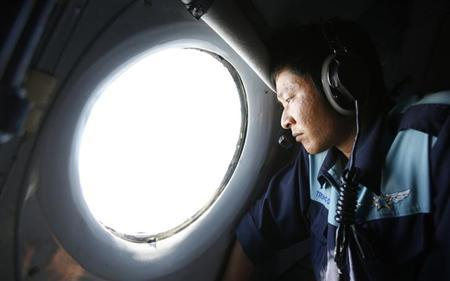 Military officer Nguyen Tran looks out from a Vietnam Air Force AN-26 aircraft during a mission to find the missing Malaysia Airlines flight MH370, off Con Dao island, March 14, 2014. REUTERS/Kham