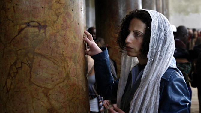 A Catholic pilgrim touches a column inside the Church of the Nativity, traditionally believed by Christians to be the birthplace of Jesus Christ, in the West Bank town of Bethlehem, Monday, Dec. 24, 2012. Thousands of Christian worshippers and tourists arrived in Bethlehem on Monday to mark Christmas at the site many believe Jesus Christ was born. (AP Photo/Adel Hana)