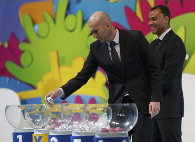 Zidane draws a ball from a pot as Cafu looks on, during the draw for the 2014 World Cup in Sao Joao da Mata