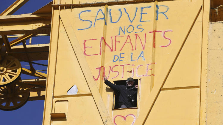 "French father Serge Charnay, who wants visiting rights with his young son and is spending a fourth day atop a crane in protest, flashes the V sign atop a crane, Monday, Feb,18, 2013. The man, wants France to strengthen its law on shared custody. He was convicted of taking his son on an unauthorized vacation for two months in 2011, and said he regretted nothing because ""if I hadn't I wouldn't have seen him."" Inscription on crane reads: Save our children from Justice.(AP Photo/David Vincent)"