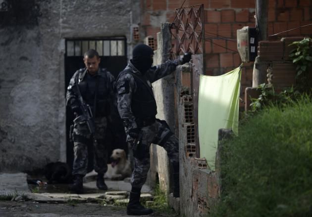 Police officers patrol and search for drugs and traffickers at the Vila Kennedy slum during an operation to install the Police Peacekeeping Unit (UPP) in the region in Rio de Janeiro