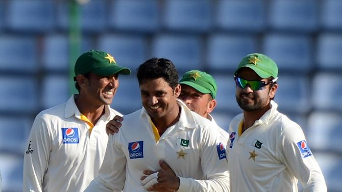 Pakistan cricketer Azhar Ali (centre) celebrates with teammates the dismissal of Sri Lanka's Dimuth Karunaratne during the opening day of the third and final Test match in Pallekele on July 3, 2015