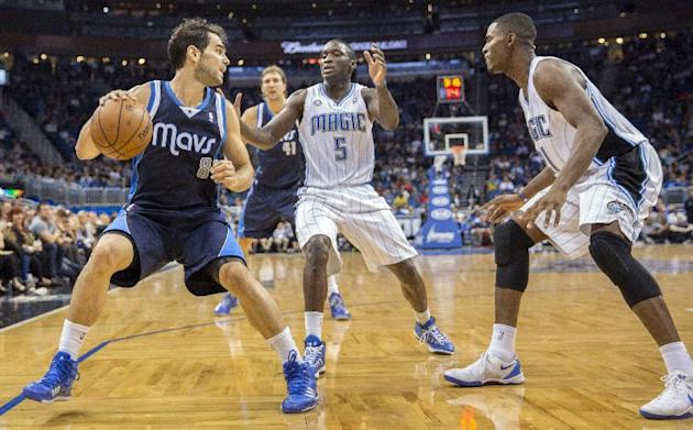 Dallas Mavericks' Jose Calderon (8) is pinned into the corner by Orlando Magic's Victor Oladipo (5) and Maurice Harkless during the second half of an NBA basketball game in Orlando, Fla., Saturday, No
