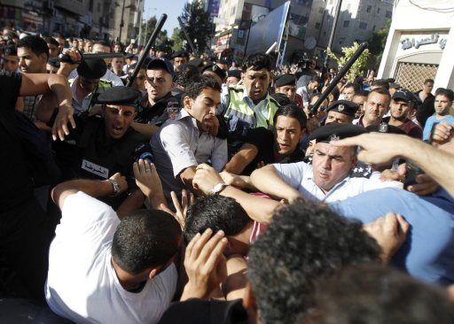 Members of the Palestinian security forces scuffle with demonstrators in Ramallah