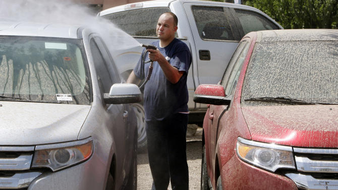 Adrian Perfetto, a lot attendant for a local car dealership, cleans off cars in the aftermath of a massive dust storm Wednesday, July 6, 2011, in Scottsdale, Ariz.   The huge dust wall that crossed the metro Phoenix area Tuesday night drastically reduced visibility, halting all flights coming in and out of Phoenix Sky Harbor Airport until conditions improved. (AP Photo/Ross D. Franklin)