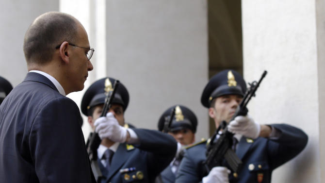 Italian Premier Enrico Letta reviews the honor guard as he arrives at Chigi palace Premier's office, in Rome, Sunday, April 28, 2013. Two Italian paramilitary police officers were shot and wounded Sunday in a crowded square outside the premier's office in Rome as Italy's new leader and his Cabinet were being sworn in a kilometer (half-mile) away. It was unclear if there was any connection between the events. (AP Photo/Gregorio Borgia)