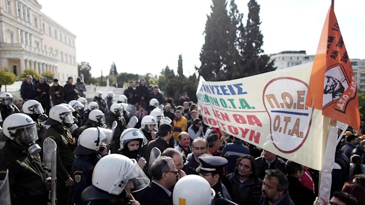 """Greek riot police prevent protesting municipal employees who pushed into the grounds of Parliament from advancing any further, during a protest in Athens on Wednesday, Dec. 12, 2012. The banner reads: """"No to sackings, the measures will not be enforced."""" Municipal employees are angry at government plans to include them on a list of state employees up for forced redundancy under the country's austerity program. (AP Photo/Petros Giannakouris)"""