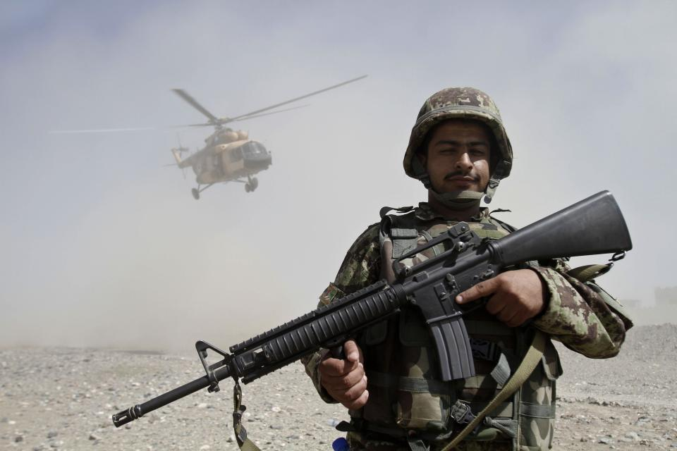 An Afghan soldier stands guard during a gathering in Gushta district of Jalalabad east of Kabul, Afghanistan, Monday, Oct. 1, 2012. Afghan Defense and Interior Ministers held a meeting with locals in Gushta district of Nangarhar about recent rocket attacks from Pakistan. (AP Photo/Rahmat Gul)