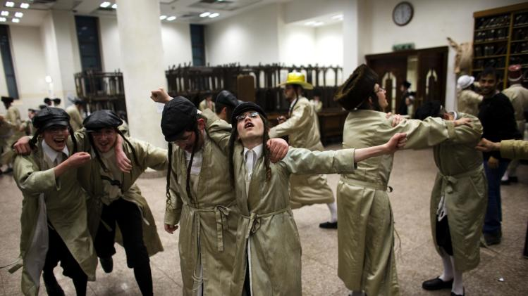 Ultra-Orthodox Jewish men dance at Toldos Aharon Yeshiva as they celebrate the holiday of Purim in Jerusalem's Mea Shearim neighbourhood