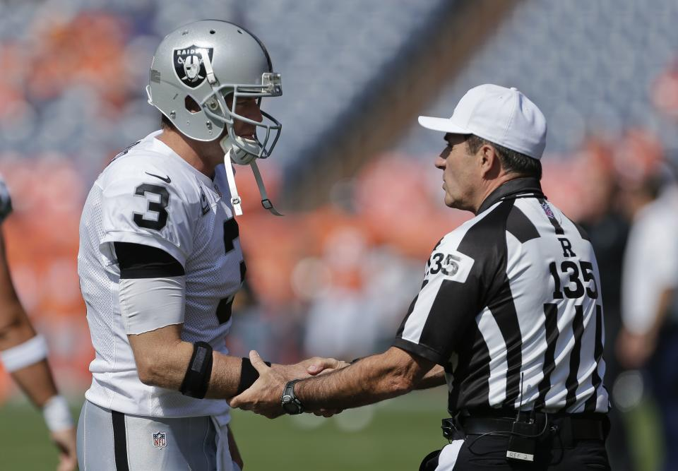 Oakland Raiders quarterback Carson Palmer (3) greets referee Pete Morelli (135) before the start of an NFL football game against the Denver Broncos, Sunday, Sept. 30, 2012, in Denver. (AP Photo/Joe Mahoney)