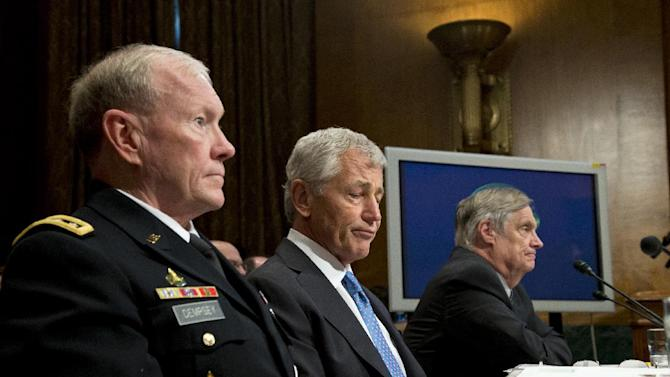 Defense Secretary Chuck Hagel, center, joined by Joint Chiefs Chairman Gen. Martin Dempsey, left, and Pentagon Comptroller Robert Hale, right, prepares testify on Capitol Hill in Washington, Wednesday, June 12, 2013, before the Senate Banking Committee hearing on President Obama's fiscal 2014 budget requests for defense spending. (AP Photo/J. Scott Applewhite)
