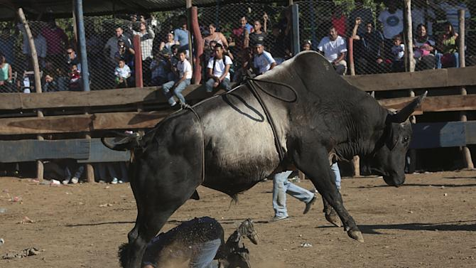 A man gets tossed by a bull during festivities honouring the capital's patron saint Santo Domingo de Guzman in Managua