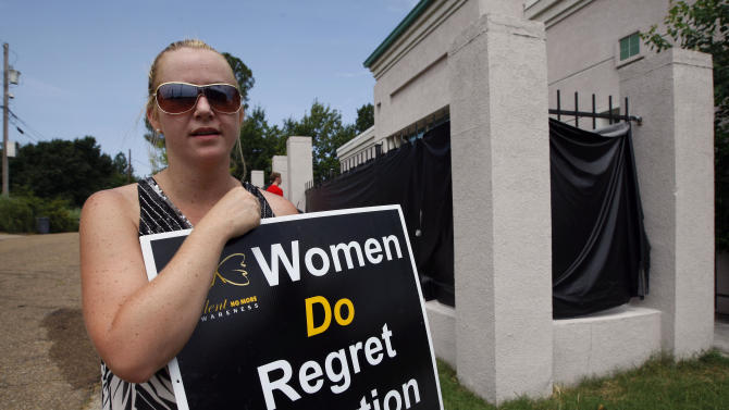 In this July 2, 2012 photo, abortion opponent Ashley Sigrest of Brandon, Miss., talks about her reasons she protests Jackson Women's Health Organization's clinic in Jackson, Miss. Sigrest said she regrets the abortion she had in August 1998 and supports admitting privileges laws because she believes they protect women's health. (AP Photo/Rogelio V. Solis)