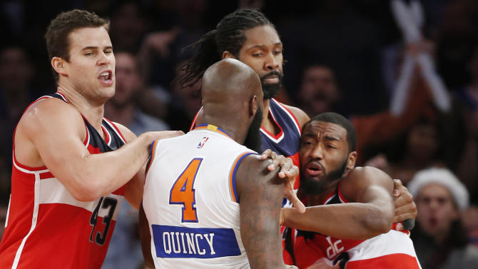Washington Wizards forwards Kris Humphries, left, and Nene Hilario (42) restrain New York Knicks forward Quincy Acy (4) who has his hand balled into a fist, and Wizards guard John Wall (2) after Acy and Wall engaged in an on-court scuffle in the second half of an NBA basketball game at Madison Square Garden in New York, Thursday, Dec. 25, 2014.  Acy was ejected from the game Wall was for a technical foul. The Wizards defeated the Knicks 102-91. (AP Photo/Kathy Willens)