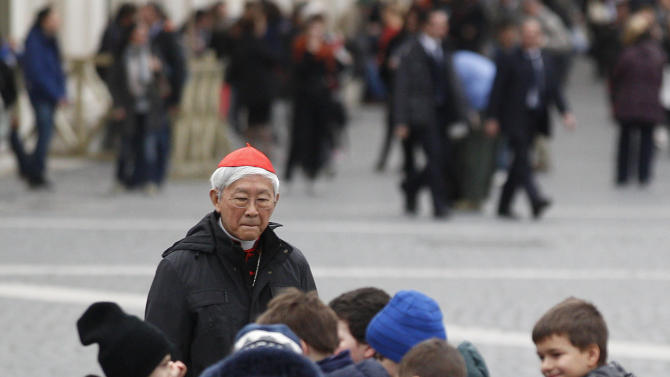 Children play in the foreground as Cardinal Joseph Zen Ze-kiun, of Hong Kong, walks in St. Peter's Square following a cardinals' meeting, at the Vatican, Thursday, March 7, 2013. Cardinals from around the world are gathered inside the Vatican on the fourth day of meetings before the conclave to elect the next pope, amid scandals inside and out of the Vatican and the continued reverberations of Benedict XVI's decision to retire. (AP Photo/Alessandra Tarantino)