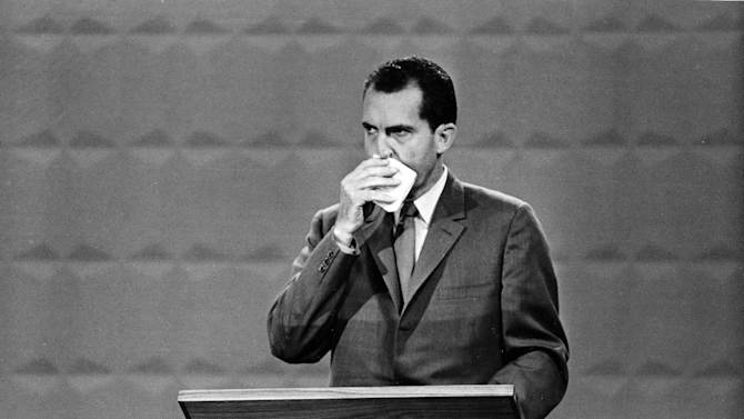 """FILE - This Sept. 26, 1960 black-and-white file photo shows Republican presidential candidate Vice President Richard M. Nixon wipes his face with a handkerchief during the nationally televised with Democratic nominee Sen. John F. Kennedy, in Chicago, Ill., Sept. 26, 1960. In presidential politics, everybody's searching for """"the moment."""" The campaigns don't know when or how it will come, but they watch for something _ awkward words or an embarrassing image _ that can break through and become the defining symbol of the other guy's flaws. Now all eyes are on the series of three presidential debates that starts Wednesday.  (AP Photo, File)"""