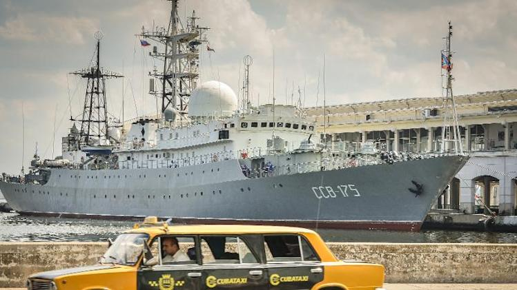 A Soviet-made Lada limousine passes by Russian Vishnya (also known as Meridian) class warship CCB-175 Viktor Leonov, docked, on February 26, 2014, at Havana harbor
