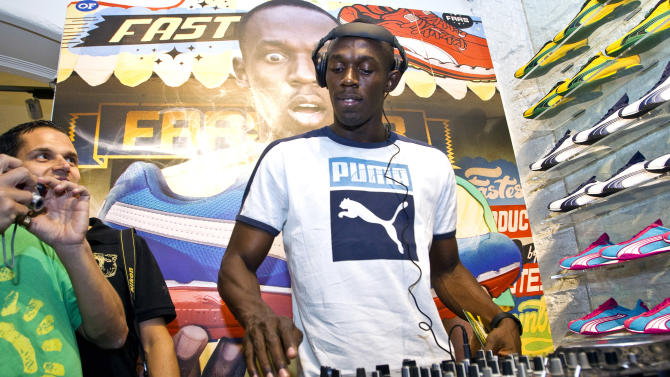 Olympic and world 100-meter record holder Usain Bolt, of Jamaica, plays as a Deejay during a visit to a shop in downtown Rome, Tuesday, May 24, 2011. Bolt will make his season debut in Thursday's Golden Gala meet in Rome, his first race since getting beat by Tyson Gay in Stockholm last August to end his two-year unbeaten streak. (AP Photo/Angelo Carconi)