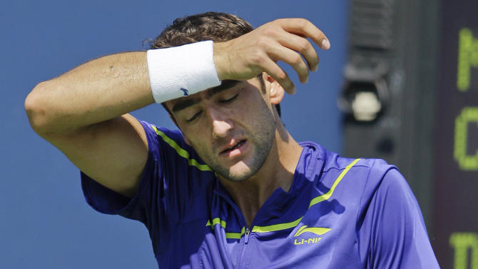 Marin Cilic, of Croatia, wipes his face during his match against Germany's Daniel Brands  in the second round of play at the 2012 US Open tennis tournament,  Thursday, Aug. 30, 2012, in New York. (AP Photo/Kathy Willens)