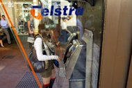 This file photo shows a woman making a phonecall from a Telstra phone booth in Sydney, in 2007. Australian telecoms giant announced on Thursday it had agreed to sell its New Zealand subsidiary TelstraClear to Vodafone for NZ$840 million ($667.5 mln)