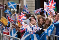 Members of the public wave flags as they wait to see members of Britain's Royal Family during the wedding of the Queen's grandaughter Zara Phillips and England rugby player Mike Tindall at Canongate church, Edinburgh, Scotland Saturday, July 30 2011. (AP Photo/Chris Clark)