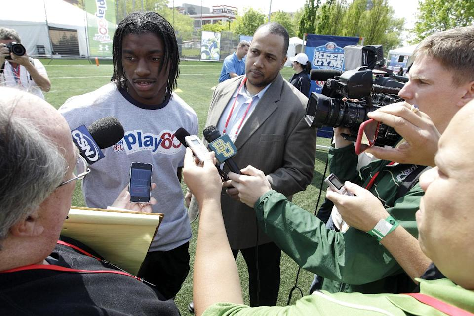 Robert Griffin III is surrounded by reporters during the NFL Play 60 Youth Football Festival, Wednesday, April 25, 2012, in New York. (AP Photo/Mary Altaffer)