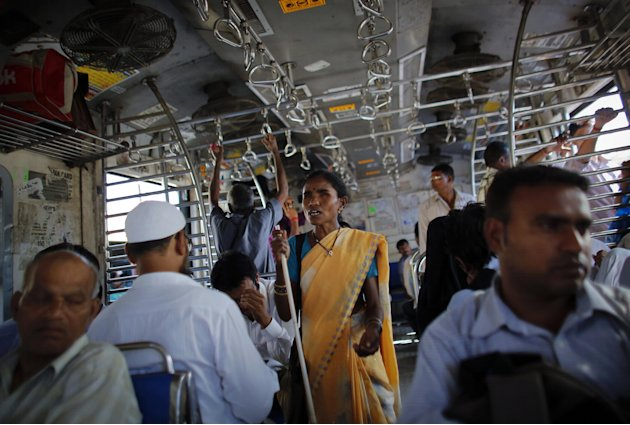 A blind woman begs for alms inside a commuter train during the evening rush hour in Mumbai
