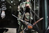 A Syrian rebel holds AK-47 rifles belonging to wounded comrades at the entrance to a hospital in the Sheikh Fares district of the northern city of Aleppo on September 18. Syrian rebels seized a crossing on the Turkish border Wednesday even as they quit a swathe of south Damascus that activists said had been reduced to a disaster area by weeks of heavy fighting