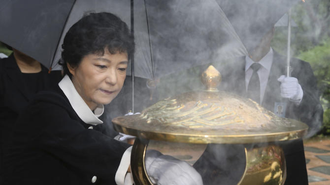 FILE - In this Tuesday, Aug. 21, 2012 file photo, Park Geun-hye, presidential candidate of the ruling Saenuri Party, burns incense in front of the tomb of her father and former authoritarian President Park Chung-hee at National Cemetery in Seoul, South Korea. Park attempts to become the country's first female president and keep the government in conservative hands in the Dec. 19, 2012 election. She has been in the public eye longer than either of her rivals and is a skilled political operator, but she is also hounded by her late father Park Chung-hee's complicated legacy, which continues to divide many South Koreans. (AP Photo/Newsis)  KOREA OUT