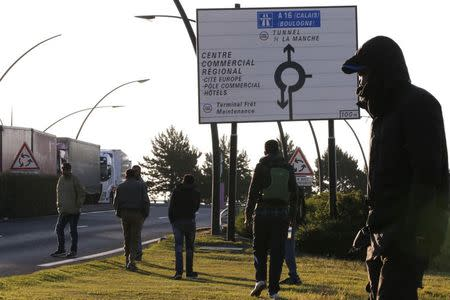 Migrants walk near the road where lorries pass after they left their hiding spot at the Eurotunnel site early in the morning in Calais