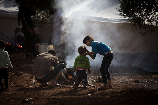 A Syrian man cooks near his sons in a refugee camp near Atma, Idlib province, Syria, Friday, Oct. 26, 2012. A powerful car bomb exploded in Damascus and scattered fighting broke out in several areas across Syria Friday, quickly dashing any hopes that a shaky holiday cease-fire would hold for four days.(AP Photo/ Manu Brabo)
