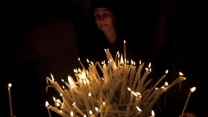 A Christian worshipper lights candles inside the Church of the Holy Sepulchre, traditionally believed to be the burial site of Jesus Christ, in Jerusalem's Old City,  Sunday, April 8, 2012. (AP Photo/Sebastian Scheiner)