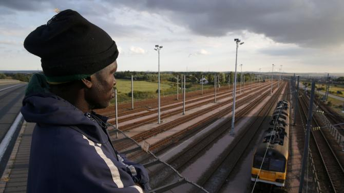 A migrant from Rwanda, who gave his name as Alex, aged 35 and is the father of two children, stands on an overpass as he watches a train pass on tracks below in Calais