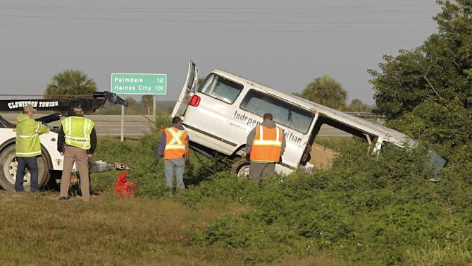 Workers pull a van out of a canal at the intersection of US 27 and State Road 78 West, Monday, March 30, 2015, near Moore Haven, Fla. Eight people were killed and 10 injured when the church van ran through a stop sign, crossed all four lanes of a rural highway and crashed into in a canal.  (AP Photo/Luis M. Alvarez)