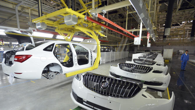 In this photo taken Wednesday, Jan. 28, 2015, a worker walks past an assembly line at a General Motors joint venture in Wuhan in central China's Hubei province. A gauge of China's manufacturing activity fell to a 28-month low in January amid economic slowdown, according to official data Sunday, Feb. 1, 2015, although January typically is a month of slower activities as China's factories prepare for the upcoming Lunar New Year celebrations. (AP Photo) CHINA OUT