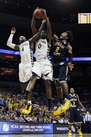 Marquette forward Jamil Wilson (0) fights for a rebound with teammate Marquette guard Todd Mayo (4) and Murray State forward Edward Daniel (2) in the second half of their NCAA third-round tournament college basketball game in Louisville, Ky., Saturday, March 17, 2012. Marquette defeated Murray State 62-53. (AP Photo/Dave Martin)