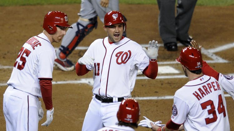 Washington Nationals' Ryan Zimmerman, center, high-fives teammates Adam LaRoche, left, Michael Morse and Bryce Harper after hitting a two-run home run in the first inning of Game 5 of the National League division baseball series against the St. Louis Cardinals on Friday, Oct. 12, 2012, in Washington. Harper scored on the homer. (AP Photo/Nick Wass)